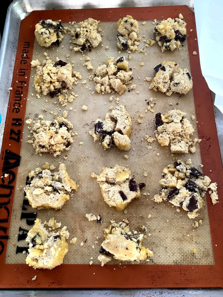 Crumbly chocolate chunk shortbread rounds on a baking sheet