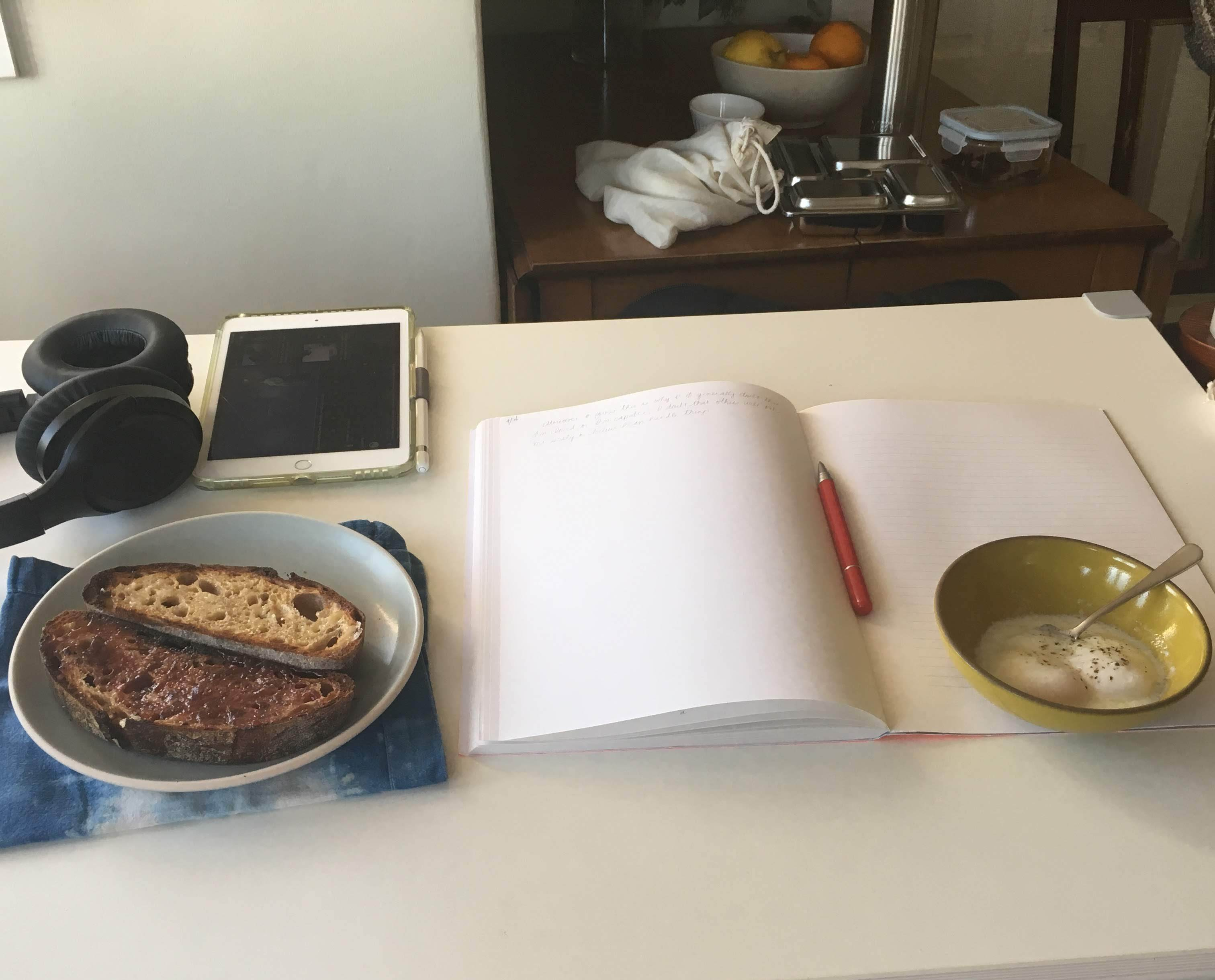 Headphones, tablet, breakfast, journal atop a desk