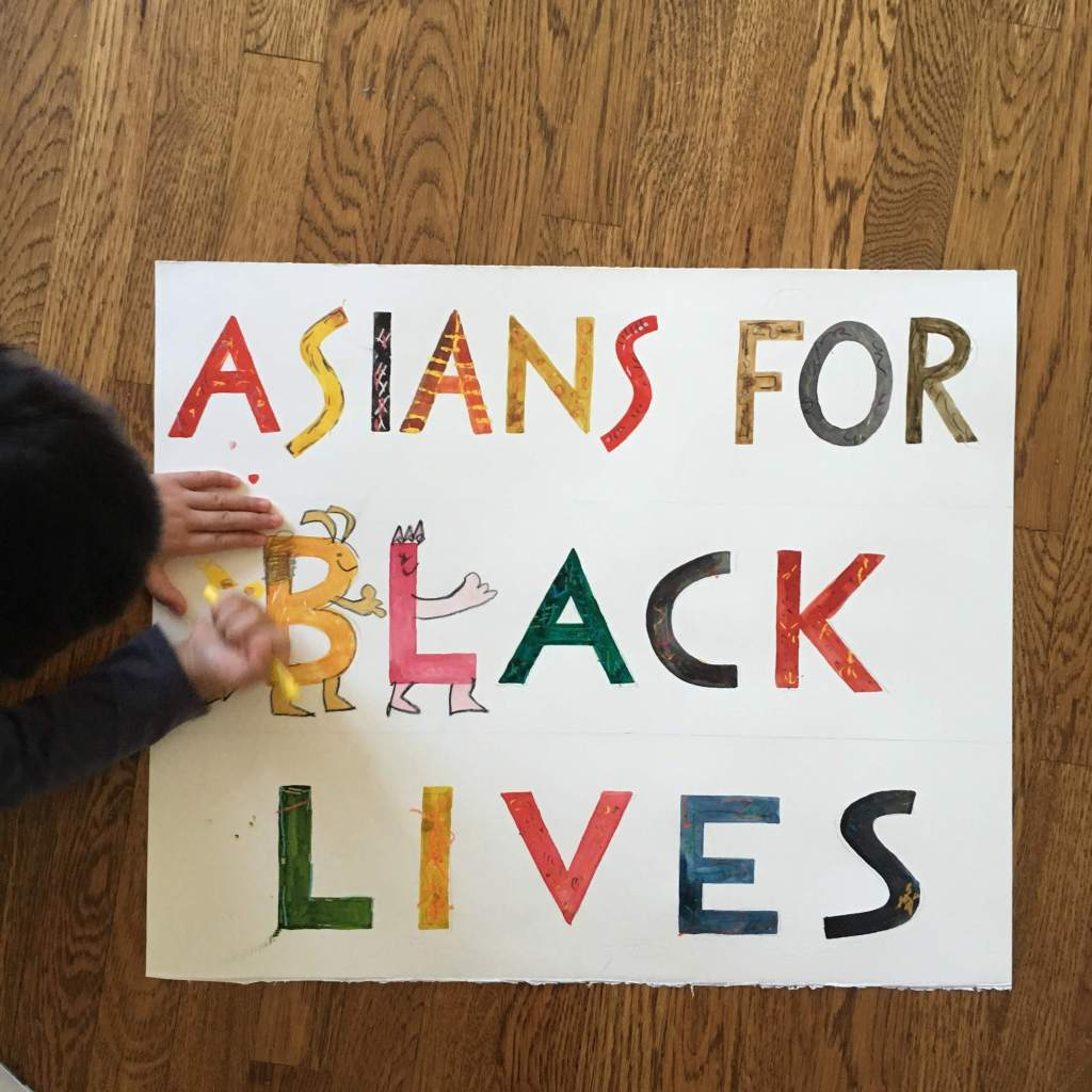 Dark-haired 4yo coloring an ASIANS FOR BLACK LIVES hand-painted sign