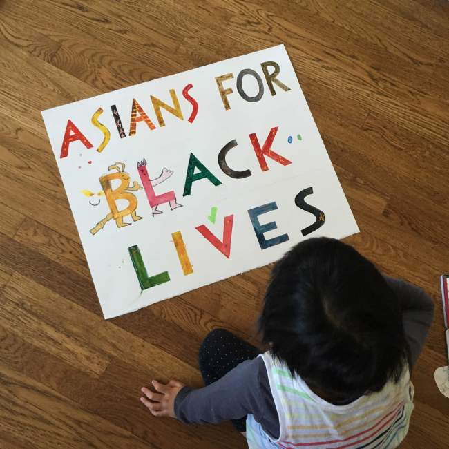 Dark-haired 4yo viewing an ASIANS FOR BLACK LIVES hand-painted sign