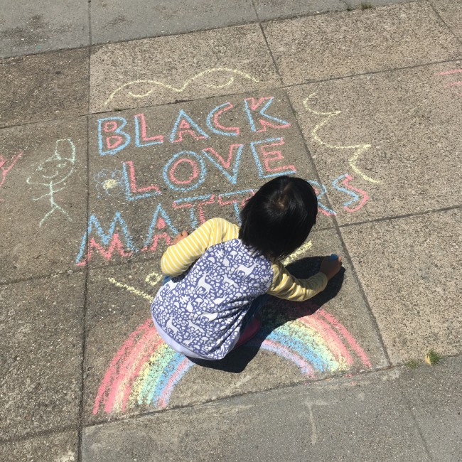 Small child decorating a sidewalk message, BLACK LOVE MATTERS