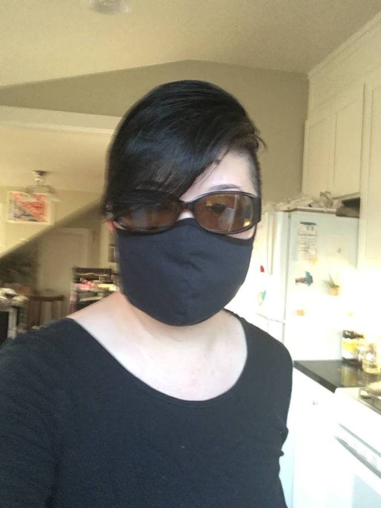 Short-haired Asian person in sunglasses and black mask, looking into the camera.