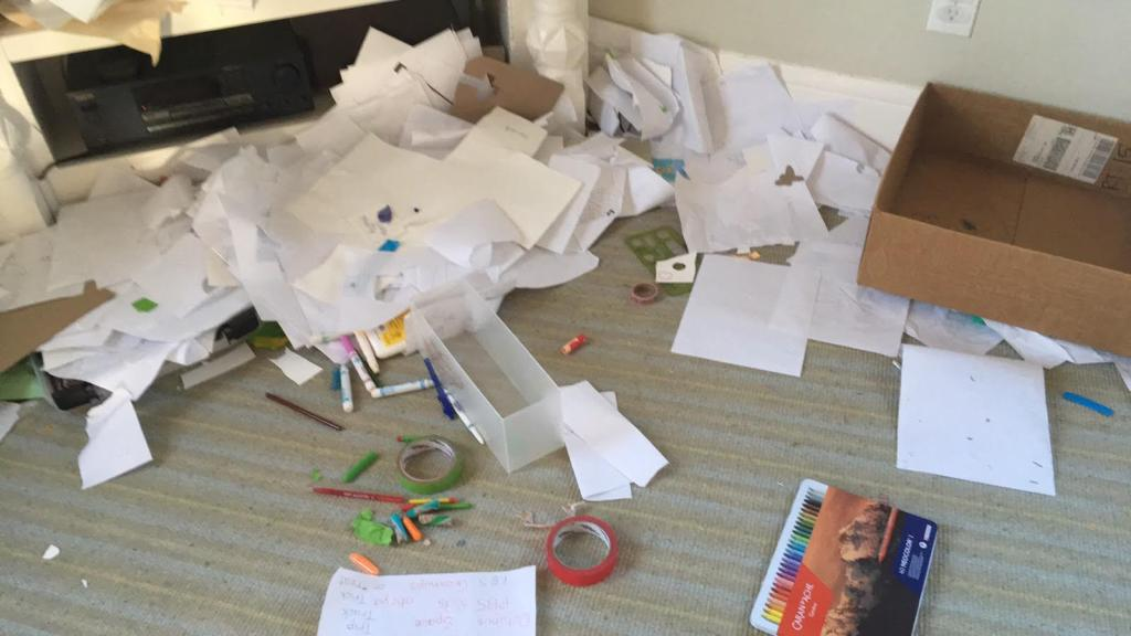 Mess of papers, art supplies, and child-drawings on a rug