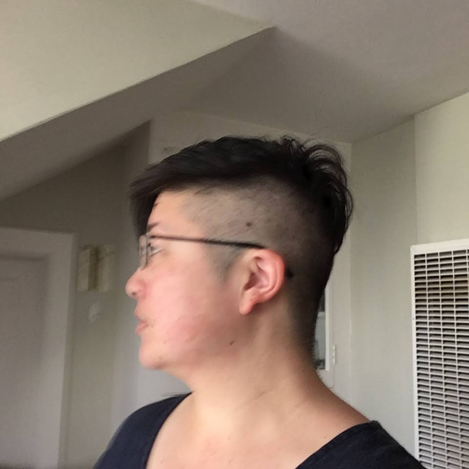 Asian person in profile with short hair and shaved side, wearing glasses