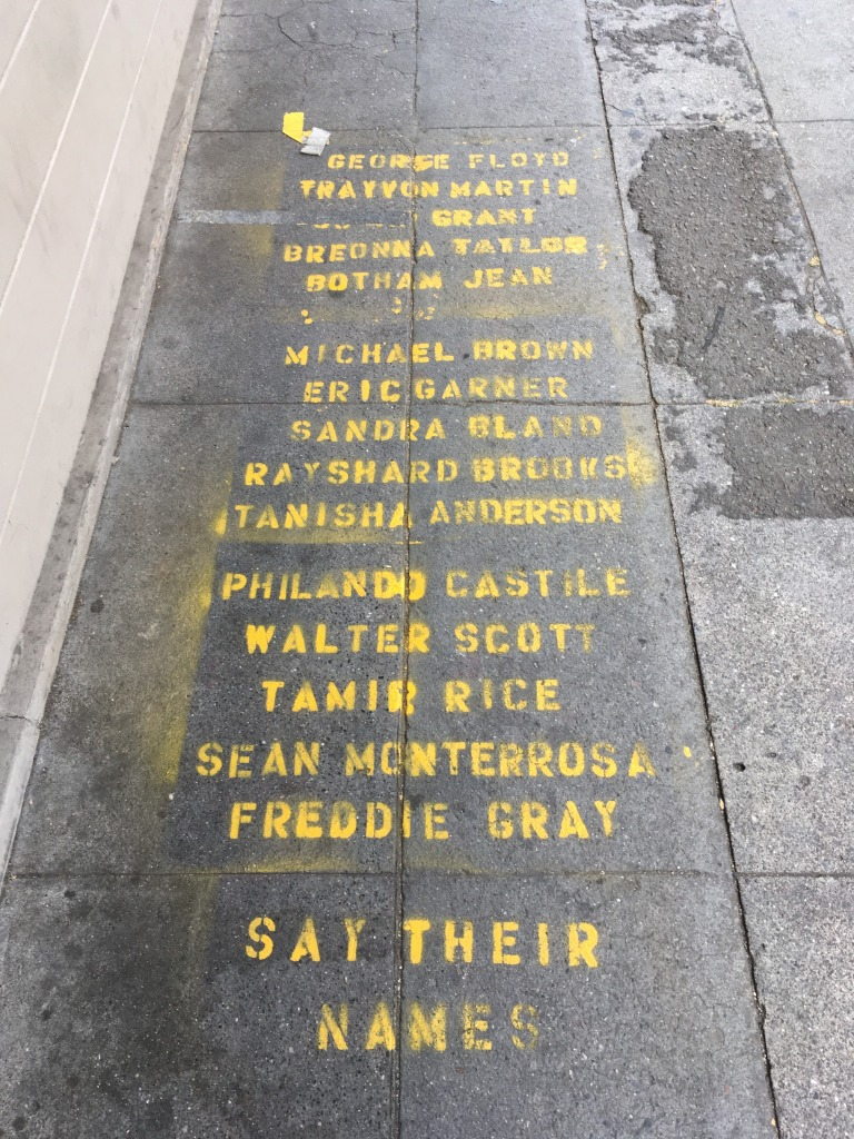 A list of names of Black people killed by police, stencilled in yellow on a sidewalk