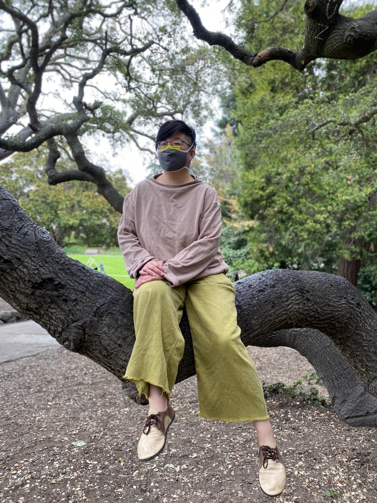 Short-haired Asian American person in face mask, taupe sweatshirt and lace-up shoes, and light green wide-legged pants sits in a tree in Piedmont Park
