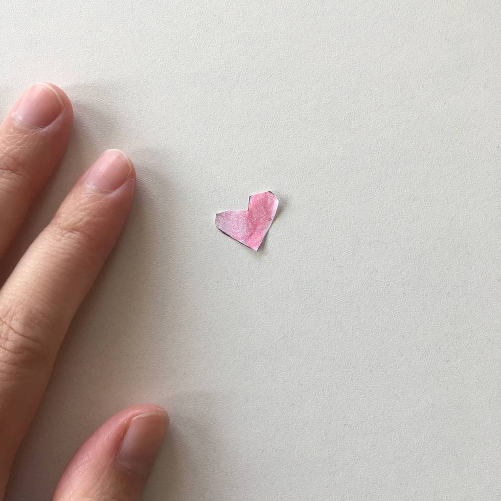 Light-skinned adult hand next to a tiny paper heart crayoned pink