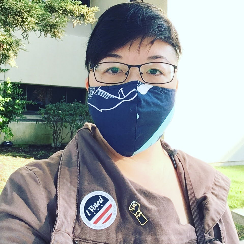 "Asian American person with glasses and a face mask, wearing an ""I Voted"" sticker and a black power fist enamel pin"