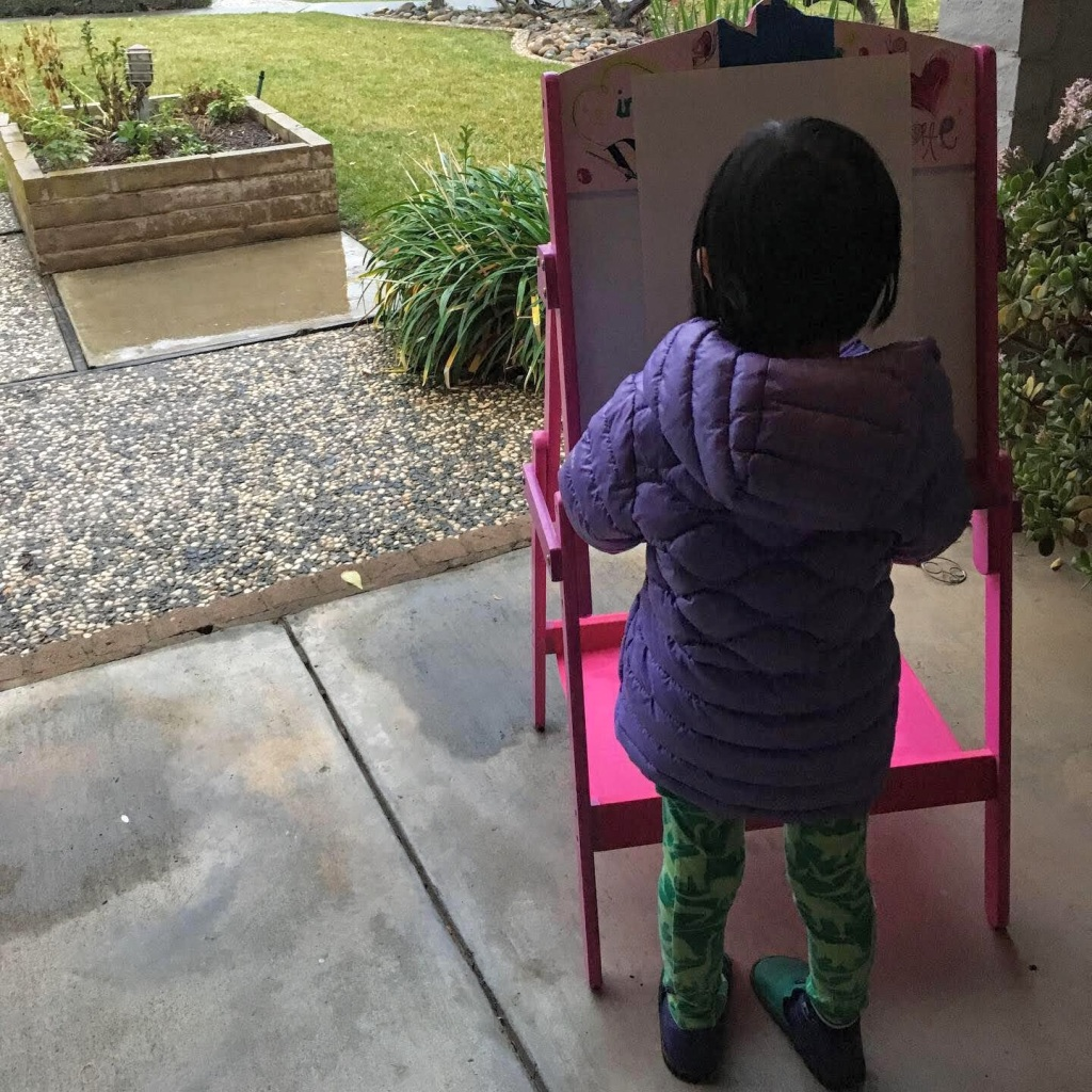 A small dark-haired child draws outdoors at an easel