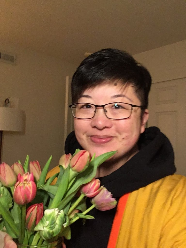 Lisa Hsia, a short-haired East Asian person with glasses, smiles while holding a bouquet of tulips.