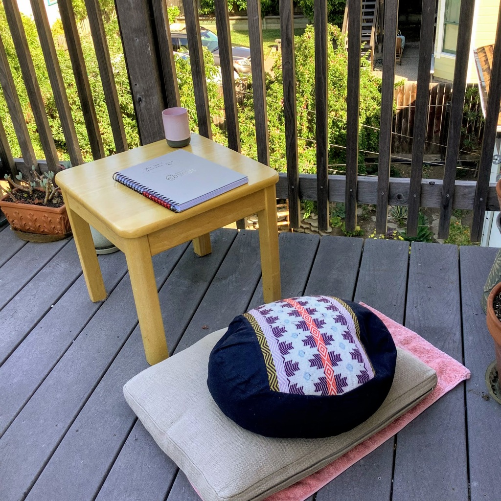 Low table, journal, and floor cushions outside on an upper-story deck
