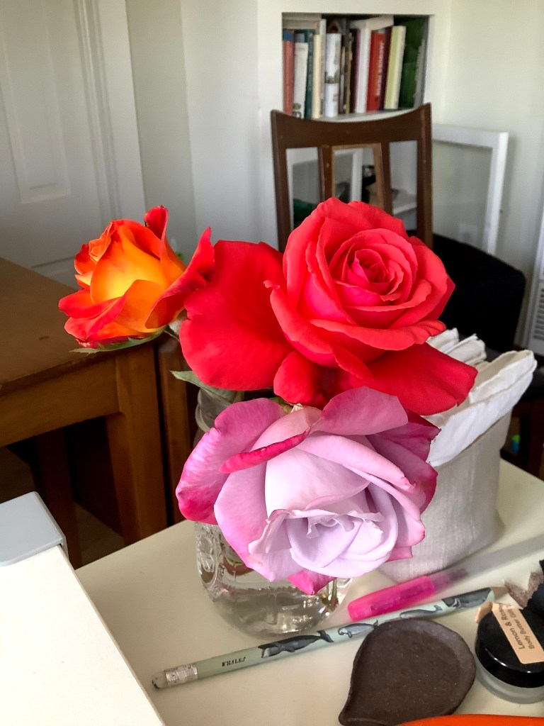 Three different-colored roses in a jar on a desk
