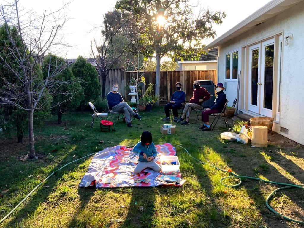A masked Taiwanese-American family  sits in a backyard near sunset