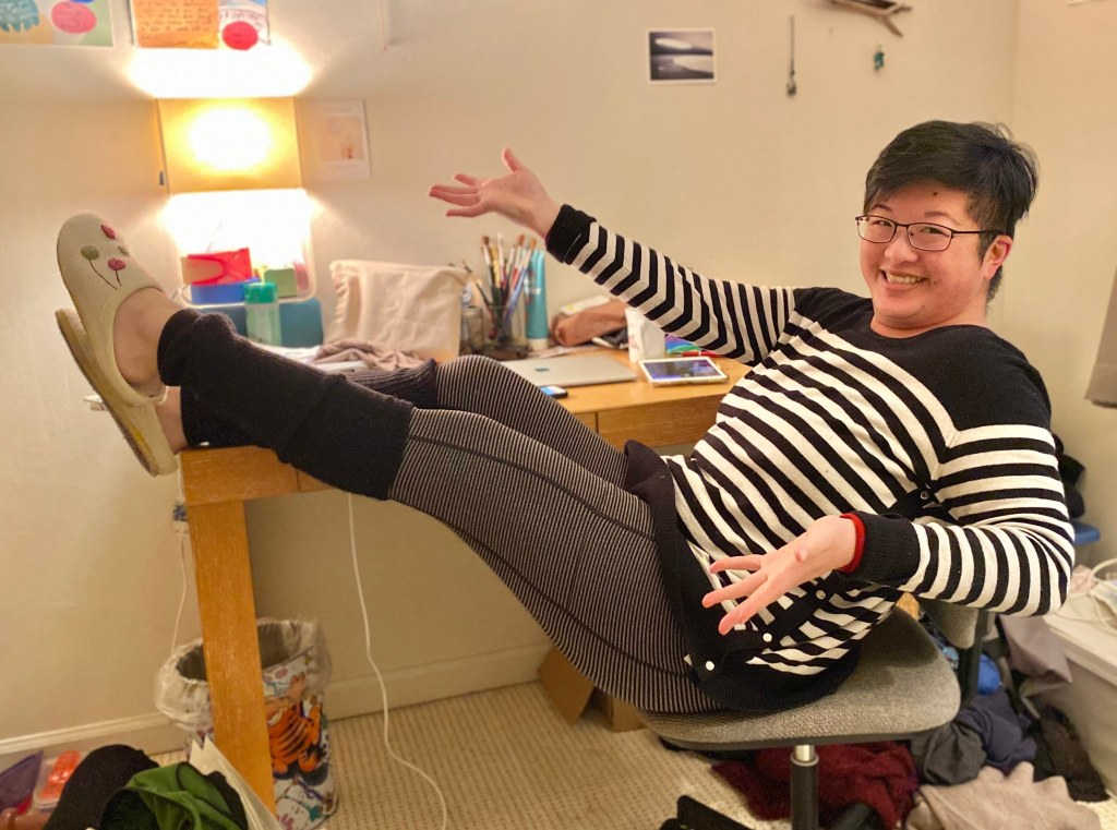 Lisa Hsia, a short-haired Asian person in glasses, shows off black leg warmers over striped leggings