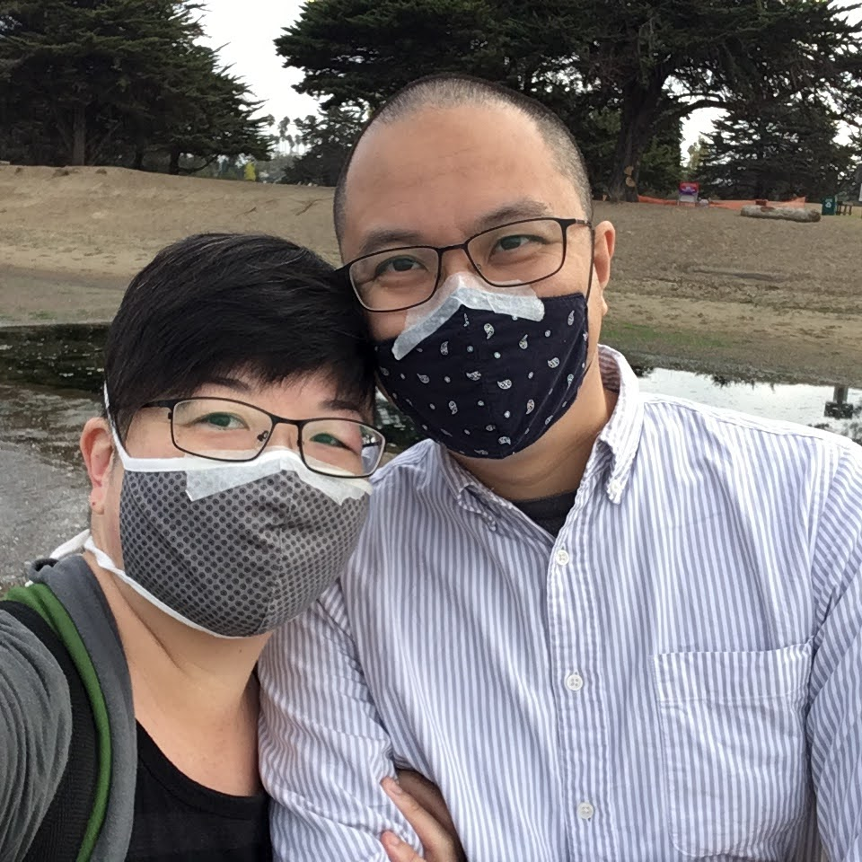 Selfie of two short-haired Asian people with glasses and face masks taped at the bridge of the nose