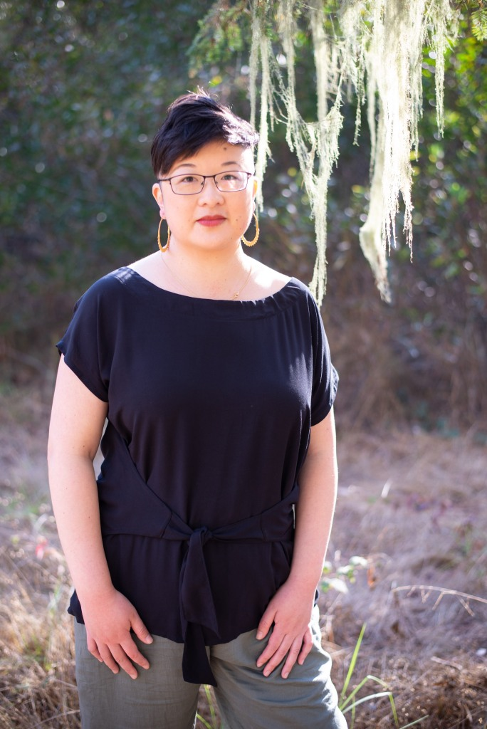 Lisa Hsia, a short-haired Asian person in glasses, stands under a tree in the sunshine