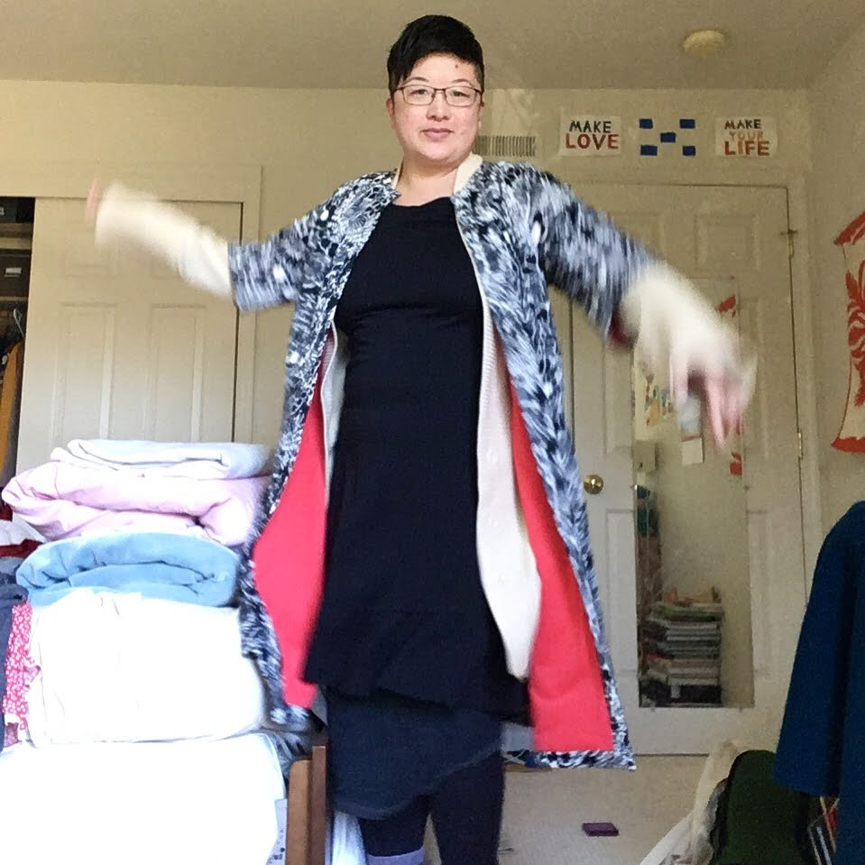 Short-haired Asian person in glasses and layered clothes dances in a bedroom