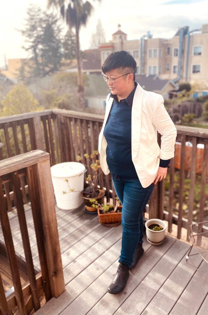 Short-haired Asian person wearing glasses, white blazer, dark skinny jeans, black boots