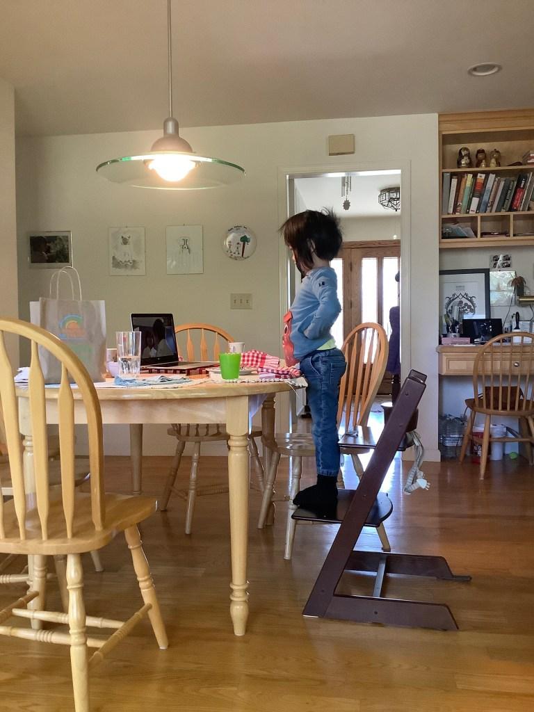 Preschooler standing on a chair looking into a laptop screen